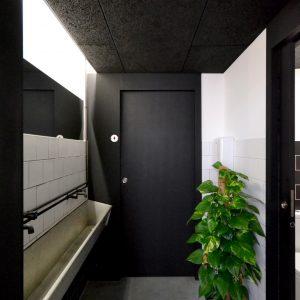 Acceso a los baños azulejo blanco y color negro