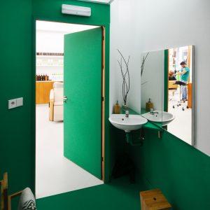 Baño en colores verde y blanco en peluquería Organic