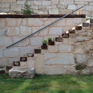 Escalera de traviesas de tren en muro de piedra