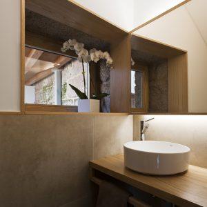 Aseo bajo escalera con luz indirecta en madera y porcelánico