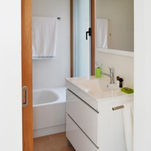 Baño con acabados blancos para vivienda en Vilaboa